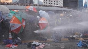 Protesters are hit by police water cannon during a demonstration against a proposed extradition bill in Hong Kong, 12 June 2019.