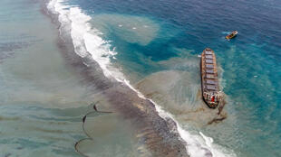 The Wakashio vessel aground on Pointe d'Esny's coral reefs with oil leaking from a crack. A floating oil boom can be seen drifting, a nearby tugboat is ready to intervene when the ship breaks, 10 August 2020.