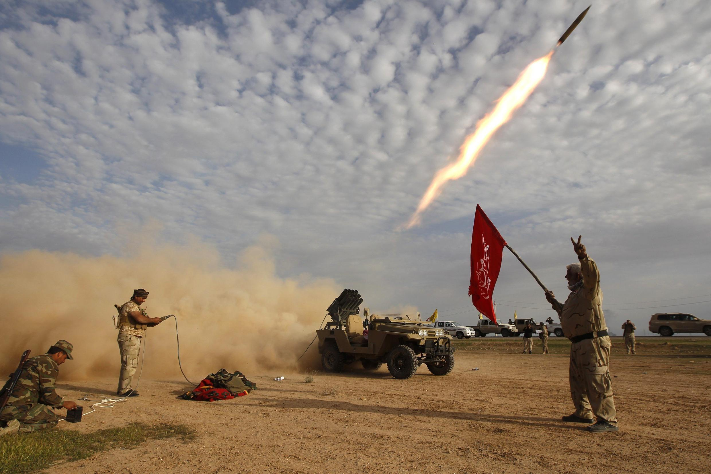 Shiite fighters launch a rocket during clashes with Islamic State militants on the outskirts of al-Alam March 8, 2015.