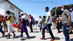 Des ouvriers haïtiens gardent leurs distances et portent un masque pour se rendre au travail à Port-au-Prince le 21 avril 2020 (image d'illustration).