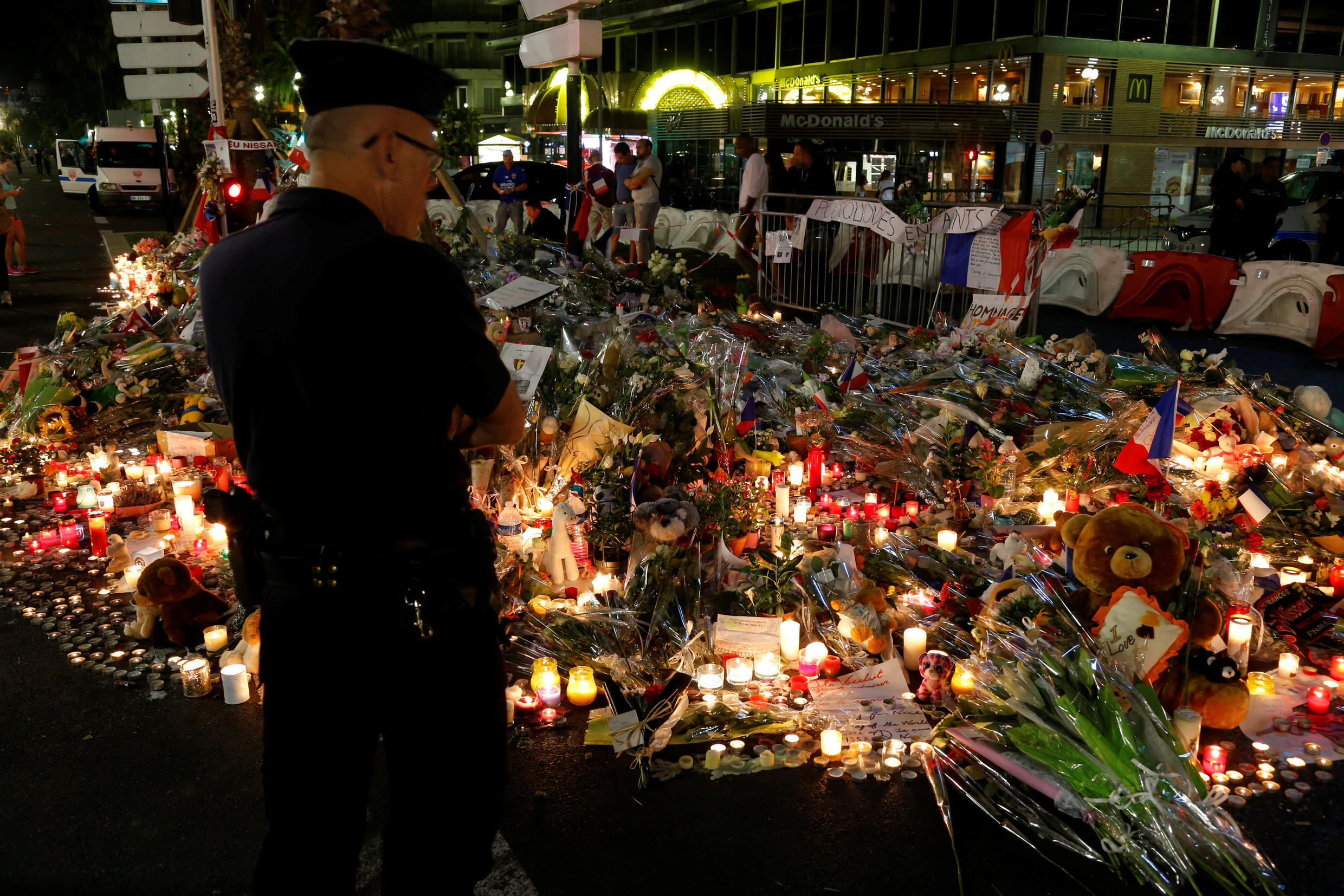 People react near flowers placed on the road in tribute to victims of the attack in Nice.