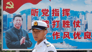 A People's Liberation Army Navy soldier stands in front of a backdrop featuring Chinese President Xi Jinping during an open day of Stonecutters Island naval base, in Hong Kong, China, June 30, 2019. REUTERS/Tyrone Siu