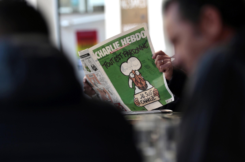 Читатель нового номера «Шарли Эбдо» в одном из кафе Ниццы, 14 января 2015.