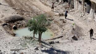 Habitantes de Aleppo em volta de um buraco provocado por um tiro de foguete.
