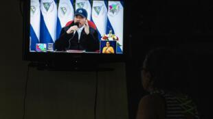 (ARCHIVO) En esta foto de archivo del 19 de julio de 2020, una mujer mira una transmisión televisiva del discurso del presidente de Nicaragua, Daniel Ortega, durante el 41 aniversario de la Revolución Sandinista.