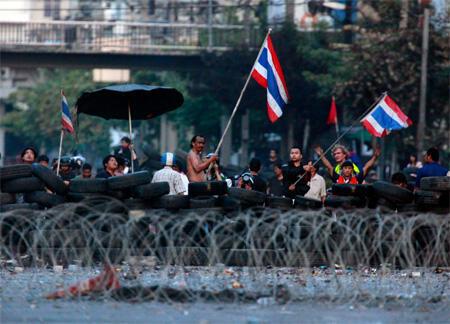 Red Shirt protesters wave the Thai flag near their barricades in Bangkok.