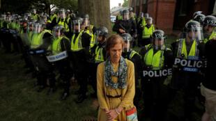 Manifestante para diante de policiais que formam um cordão de segurança em Charlottesville, neste sábado