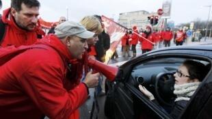 Servidores conversam com motorista em avenida bloqueada pelos grevistas em Bruxelas.
