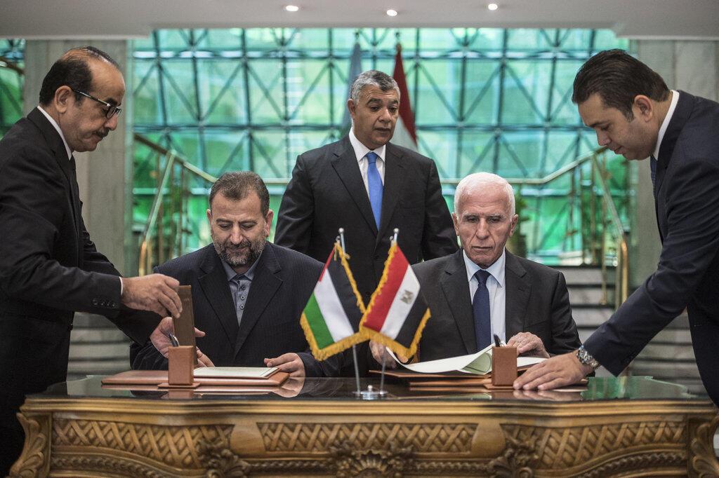 Azzam al-Ahmad, do Fatah (à direita), e Saleh al-Aruri, do Hamas (à esquerda), assinam um acordo de reconciliação - Cairo, 12 de Outubro de 2017.