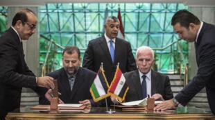 (Photo d'illustration) Azzam al-Ahmad, du Fatah (à droite), et Saleh al-Arouri, du Hamas (à gauche), signant un accord de réconciliation au Caire le 12 octobre dernier.