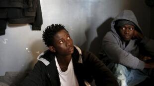 Dois jovens que tentavam viajar sozinhos, fotografados em março de 2015 no centro de detenção para migrantes em Garabulli, na Líbia.
