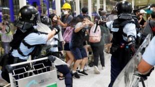 La police anti-émeute utilise un spray au poivre pour disperser des manifestants à l'aéroport international de Hong Kong, le 13 août 2019.