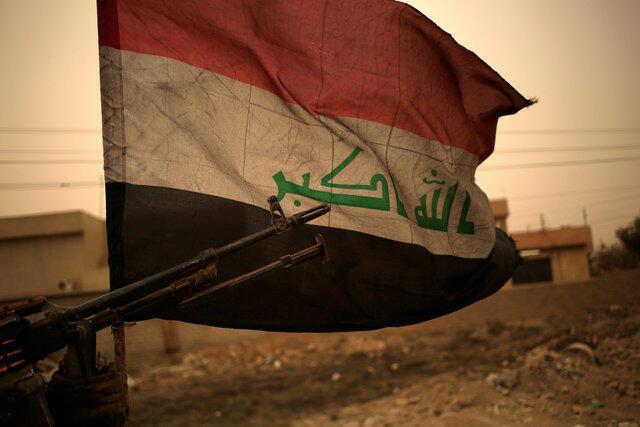 Bandeira do Iraque enterrada na areia a leste de Mossul, em 1° de novembro de 2016