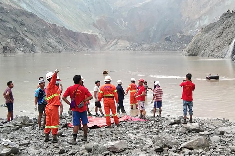 Bombeiros nas margens do lago do vale de Hpakant,em Myanmar, onde ocorreu o desmoronamento da mina de jade que provocou mais de 100 mortos
