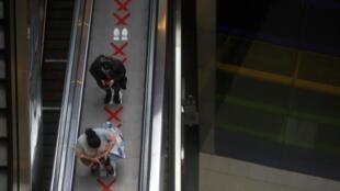 Des Péruviens sur l'escalator d'un centre commercial de Lima le 22 juin 2020.