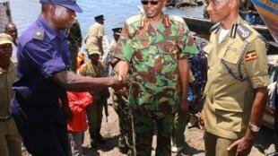 Joseph Boinett( Katikati )akisalimiwa na polisi wa Uganda, akiangaliwa na Kale Kayihura (Kulia)