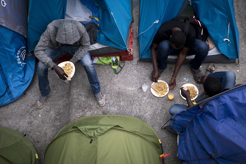 Des migrants à l'entrée de leurs tentes dans le camp situé près de la gare parisienne d'Austerlitz, le 14 juin.