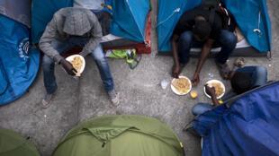 Des migrants à l'entrée de leurs tentes, dans le camp situé près de la gare parisienne d'Austerlitz.