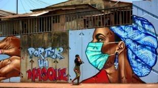Graffiti de prévention pour le port du masque sur l'autoroute Fidel Castro à Conakry.