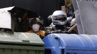 Supporters of the Kiev government take cover during clashes with pro-Russia activists in the streets of Odessa, 2 May, 2014