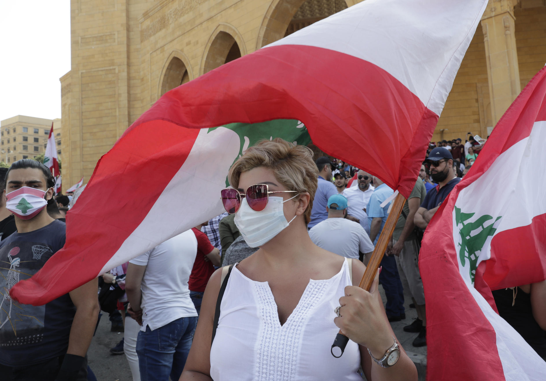 Una mujer lleva una bandera libanesa durante la protesta antigubernamental en el centro de Beirut, el 6 de junio de 2020