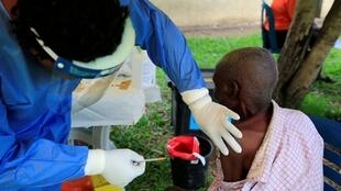 A Ugandan health worker administers Ebola vaccine to a man in Kirembo village, near the border with the Democratic Republic of Congo, 16 June 2019.