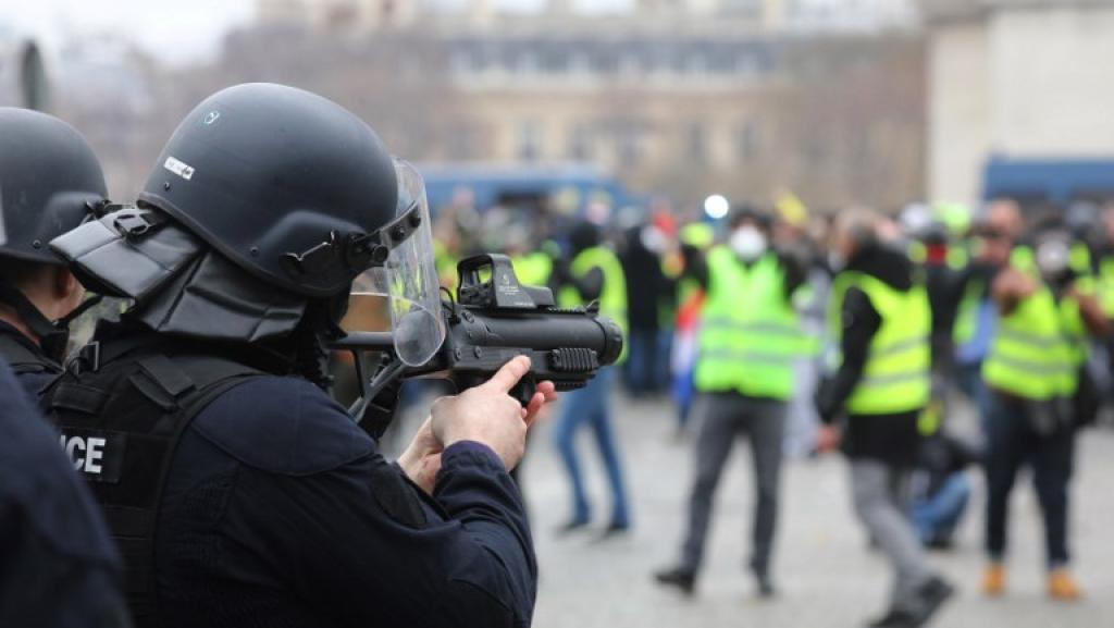 A French police officer aims a Defence Ball Launcher (LBD) at a crowd of Yellow Vest protesters at place de la Bastille in central Paris, 12 January 2019