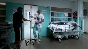 A doctor walks next to a patient walking with his infusion and another patient lying on a hospital bed in the corridor at the emergency department of the Delafontaine hospital in Saint-Denis, suburb of Paris, on July 17, 2020.