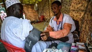 Un médecin soudanais mesure la pression sanguine d'un manifestant aux abords du QG de l'armée à Khartoum, le 19 avril 2019.