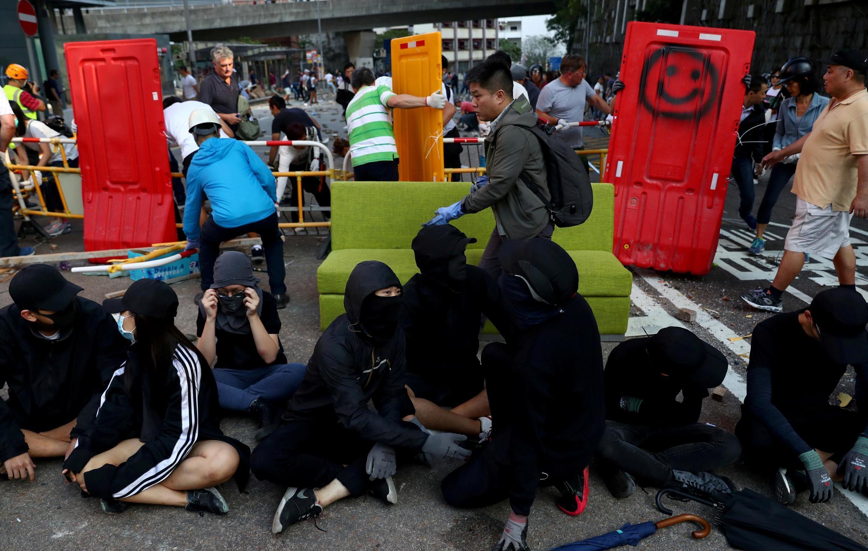 Người biểu tình ngồi trong khi dân cư địa phương dỡ một hàng rào bên ngoài Đại học Hồng Kông, ngày 16/11/2019.