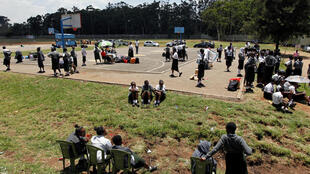 Students sit at the basketball court at the State House Girls High School following a directive by the Kenyan government to suspend learning in all schools as a preventative measure against coronavirus disease (COVID-19) fears, in Nairobi, Kenya March 16, 2020. REUTERS/Njeri Mwangi