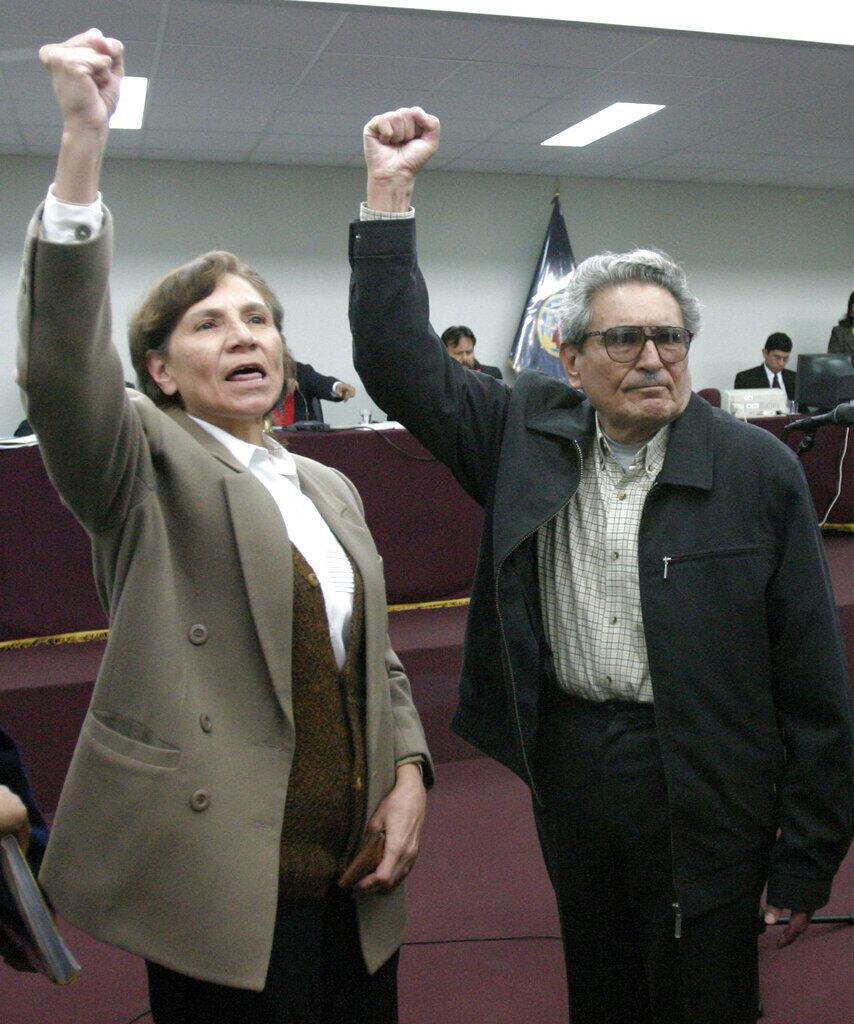 En esta foto de archivo del 5 de noviembre de 2004, Abimael Guzmán, fundador y líder del movimiento guerrillero Sendero Luminoso, a la derecha, y Elena Iparraguirre, compañera y amante, levantan el brazo durante el primer día de su juicio civil en la Base Naval de Callao, Perú.