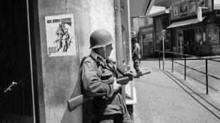 In this May 15, 1962 file photo, a French soldier guards a street corner in Oran, Algeria. On the wall is a poster of the nationalist Secret Armed Organization, calling for citizens to take up arms against Algerian independence.