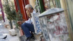Un vendeur devant sa boutique dans les rues d'Athènes, le lundi 13 juillet.
