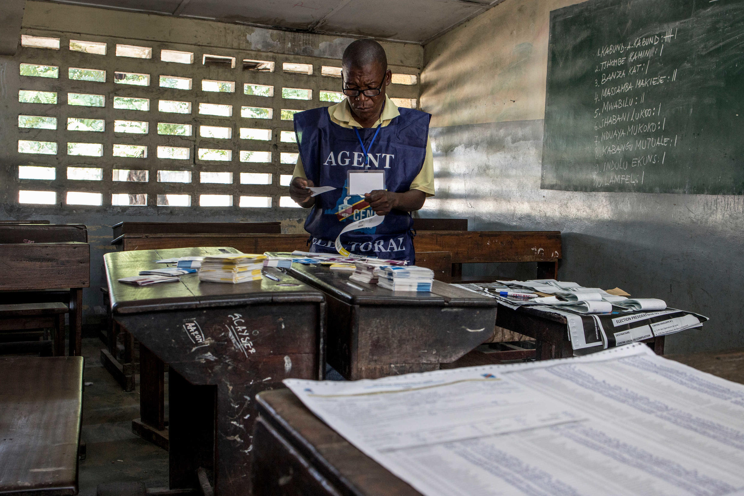 An electoral official arranges ballot papers at a polling station in Kinshasa the morning after the vote, 31 December 2018.