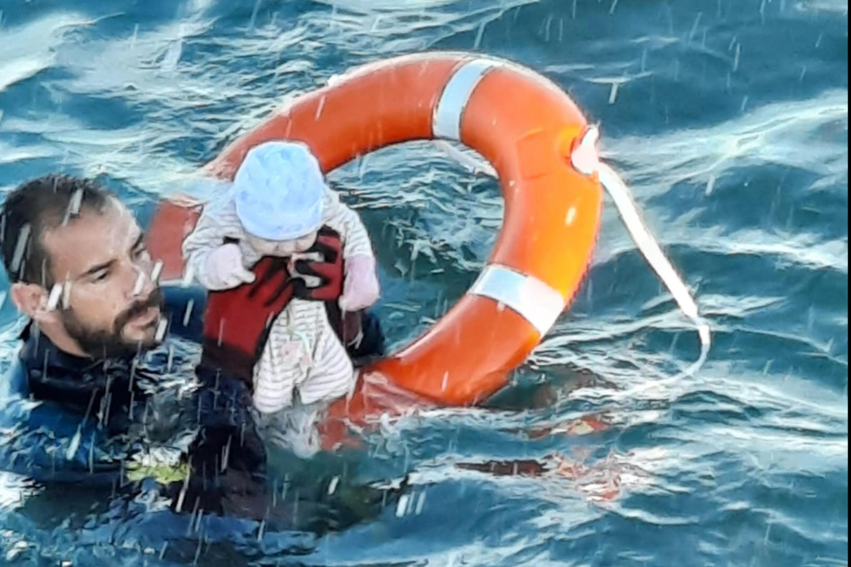 Một trẻ sơ sinh được một nhân viên cứu hộ vớt ngoài khơi Ceuta, Tây Ban Nha, ngày 19/05/2021.