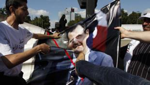 Turquía: un opositor sirio destruye un cartel con la imagen del presidente Bashar Al Assad durante una manifestación en Estambul, el 28 de agosto de 2011.