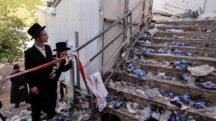 Ultra Orthodox Jews look at stairs with waste on it in Mount Meron, northern Israel, where fatalities were reported among the thousands of ultra-Orthodox Jews gathered at the tomb of a 2nd-century sage for annual commemorations that include all-night prayer and dance, April 30, 2021.