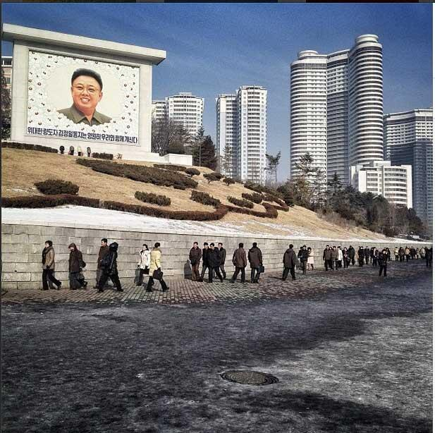 Des habitants de Pyongyang devant une mosaïque de l'ancien dirigeant Kim Jong il.