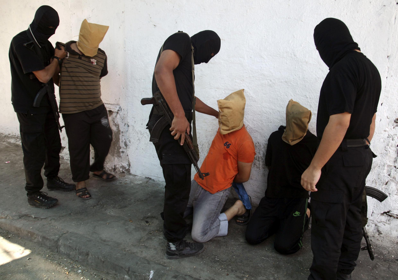 Miembros del Hamas (en negro) llevando a los palestinos sospechosos de haber colaborado con Israel minutos antes de que fueran ejecutados, Gaza, 22 de agosto de 2014.