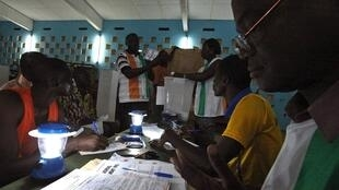 Polling workers count the ballots at a polling station in Gagnoa in western Ivory Coast