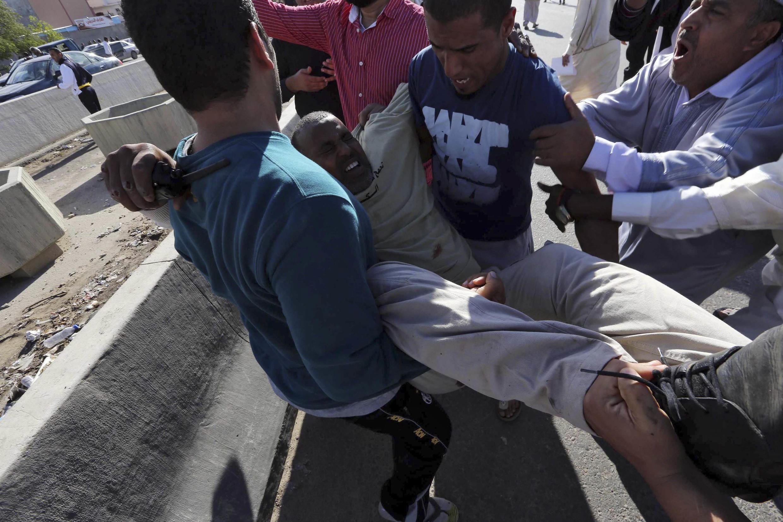 Un blessé transporté après les tirs d'une milice contre la foule venue demander son départ, le 15 novembre 2013 à Tripoli, en Libye.