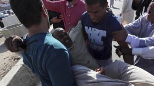 Un blessé transporté après les tirs d'une milice contre la foule, le 15 novembre 2013 à Tripoli, en Libye.