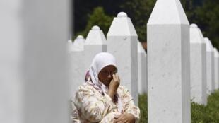 Một phụ nữ Hồi giáo bên mộ người chồng bị sát hại ở Sebrenica.
