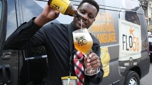 John Christian Kavakure pours his beer brand Yellow Flo into a custom made glass.