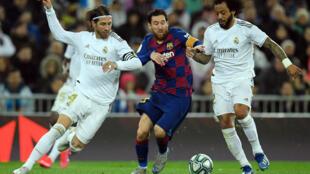 Lionel Messi trata de pasar entre Sergio Ramos (izq) y Marcelo durante el partido liguero entre el Real Madrid y el FC Barcelona disputado el 1 de marzo de 2020 en el estadio Santiago Bernabéu