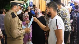 Un policier marocain distribue des masques pour lutter contre la propagation du coronavirus à Marrakech, en août 2020.