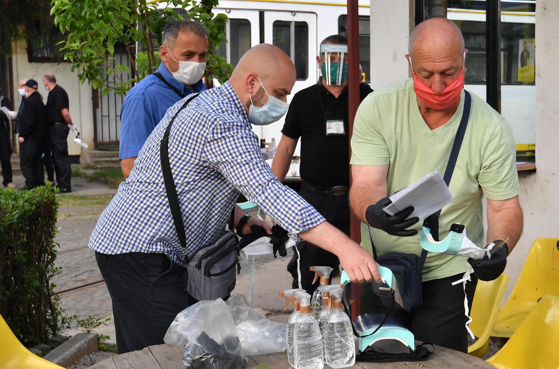 Condutores de trens da Bósnia retiram seus kits de proteção (máscaras, luvas e gel hidroalcoólico) antes de recomeçar o trabalho, após dois meses de confinamento em Sarajevo, em 15 de maio de 2020.
