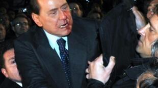 La police raccompagne le Premier ministre italien Silvio Berlusconi à sa voiture après l'agression dont il a été victime dimanche 13 décembre à Milan.