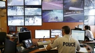 Police officers monitor control screens in the command room of security of proximity of the Paris Police Prefecture